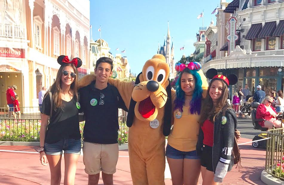Seniors take a photo with Disney character, Pluto, in Disney's Magic Kingdom park.