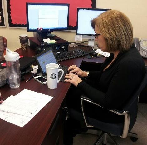 Mrs. Suarez enjoys a cup of Starbucks coffee while working hard.