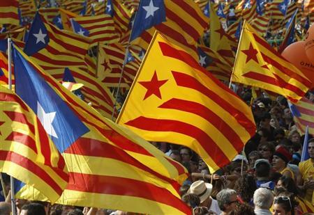 Catalan nationalist flags flow through the air as those holding them demand their independence.