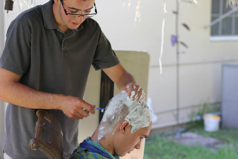 Austin Herrin, the person who initially thought of the idea, shaving the head of Oliver Robles.