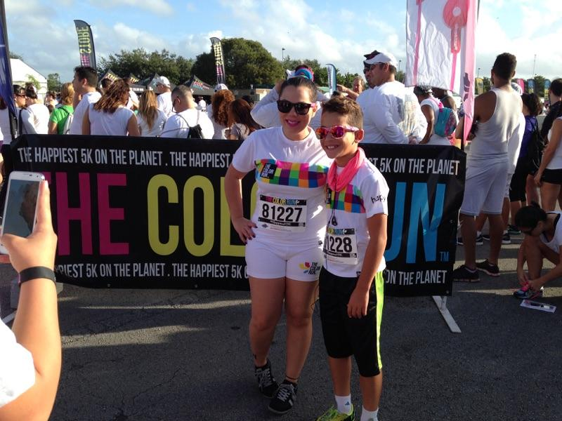 Two participants pose in front of the Color Run sign before the race.