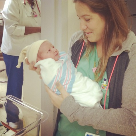 Fletcher holding the first baby delivered in South Florida of 2015.