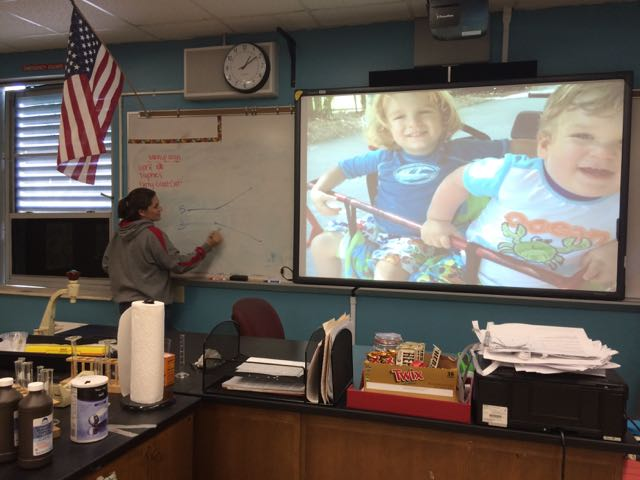 De La Vega teaches her students about DNA replication. Her two sons are larger-than-life as her screensaver.