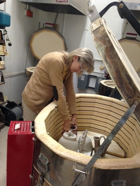 Ms. Stapleton placing students' clay pieces in the kiln.