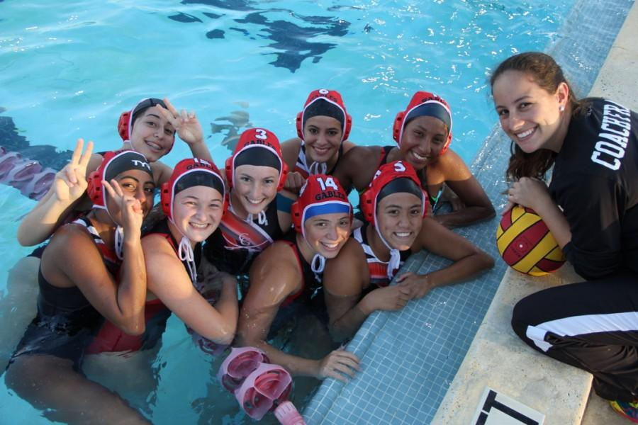 Coach Fraga and the girls water polo team huddle during a break.