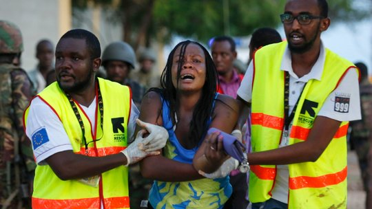 Kenyan authorities help students and citizens out of the University during the shooting.