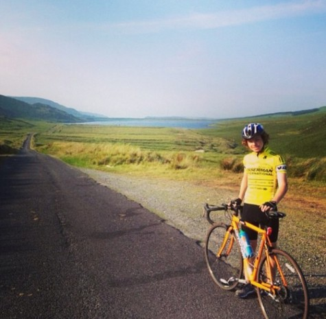 Zack Walsh biking through the green terrain of Ireland.