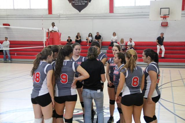 The girls volleyball team huddling up before their set