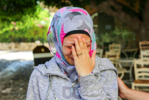 This refugees is crying as she remembers the events that occurred as she moved to Greece including the death of her husband.
