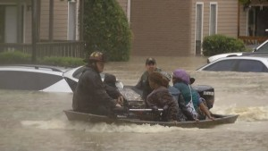 Firefighters have to use boats to rescue people trapped in their homes.