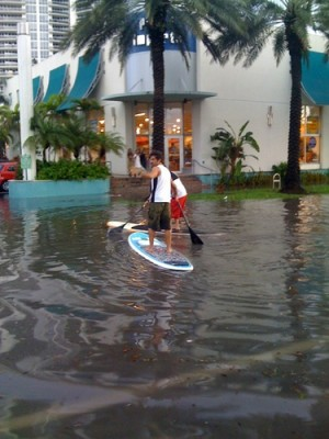 Locals take advantage of the flooded streets to paddle board.