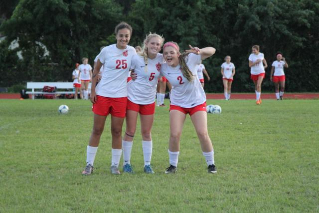 Three of the girl's soccer team very satisfied with themselves after their victory
