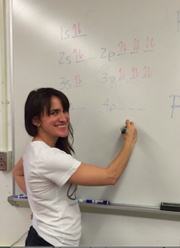 Ms. Kiely explaining a chemistry problem on the board