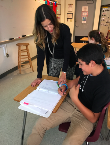 Ms. Gonzalez helping a student with their work