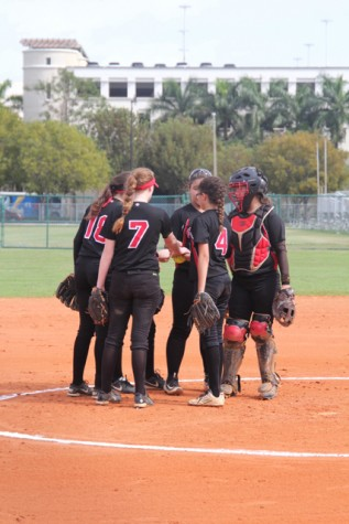 The softball team huddles up as they begin their inning