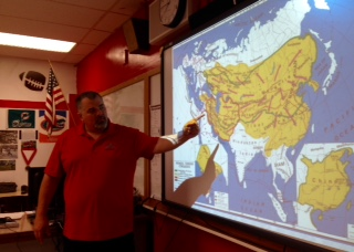 Mr.Miller explaining map with his students, doing what he loves.