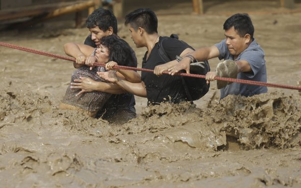 A group of people stranded in a mudslide hold on to a rope as they make their way to safety.