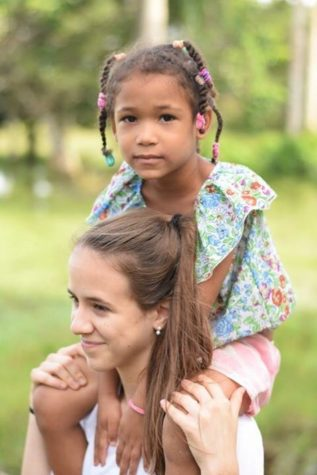 Marina Torras stands with a child from the village.