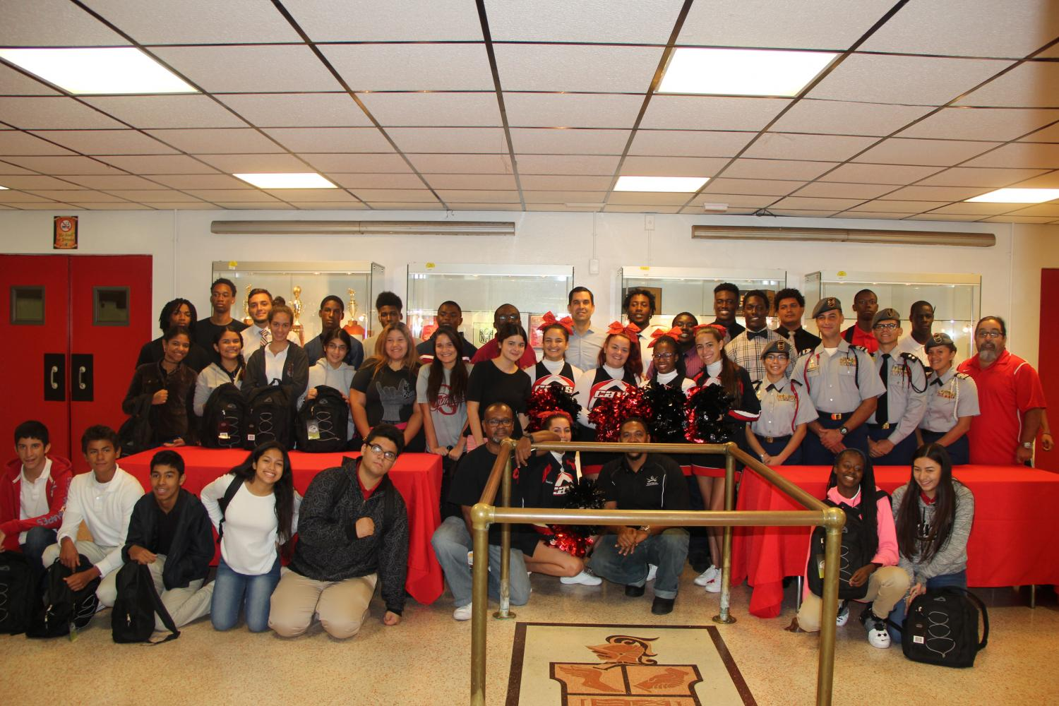 Gables students smile for a picture with Commissioner Lago in the auditorium lobby.