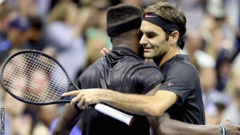 Frances Tiafoe (left) and Roger Federer embrace after Federer's hard-fought victory over 5 sets.