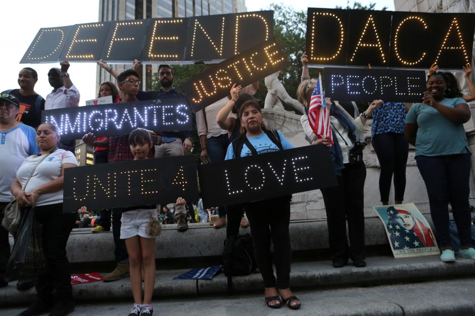 FILE PHOTO - People hold signs against U.S. President Donald Trumps proposed end of the DACA program that protects immigrant children from deportation at a protest in New York City, U.S., August 30, 2017. REUTERS/Joe Penney