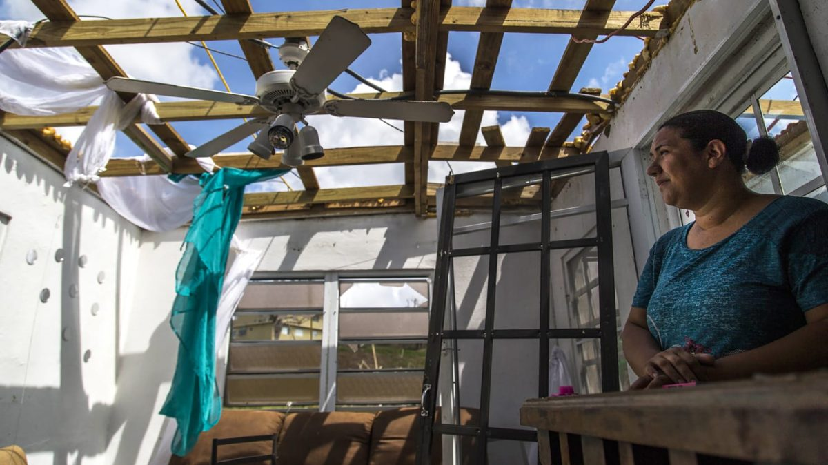 A woman stands, in what used to be her home, after Hurricane Maria has passed.