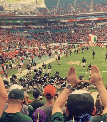 University of Miami fans raise tehir hands in celebration the team's win.