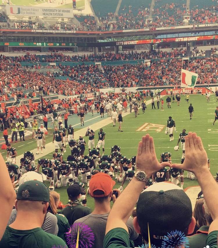 University of Miami fans raise tehir hands in celebration the team's win.