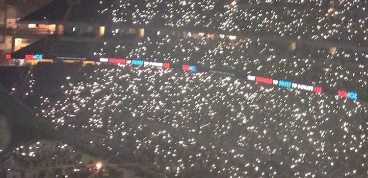 Crowd lighting up the stadium in support