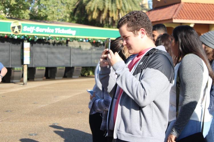Junior Alain Perez takes a photo of his friends.