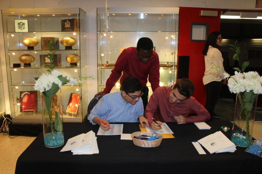 Volunteers sign students in.