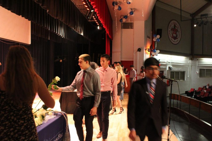 IB Junior students walk across the stage to get pinned.