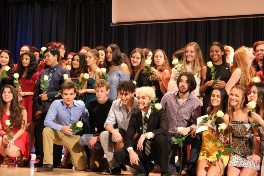 Newly inducted IB students pose for a group photo on stage.