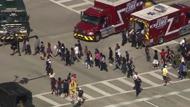 Students+at+high+school+being+led+outside+the+school+onto+the+street+near+firetrucks.
