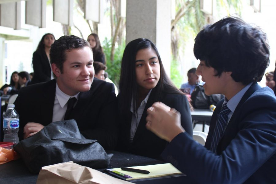 Sophomore+Jesse+Zambrano+and+junior+Alain+Perez+discuss+with+delegates+possible+resolutions+for+their+committees.+
