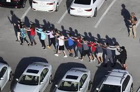 Estudiantes de la secundaria ubicada en Parkland siendo movidos en cadena de forma segura hacia donde se encontraba el Centro de control y os carros de bomberos.