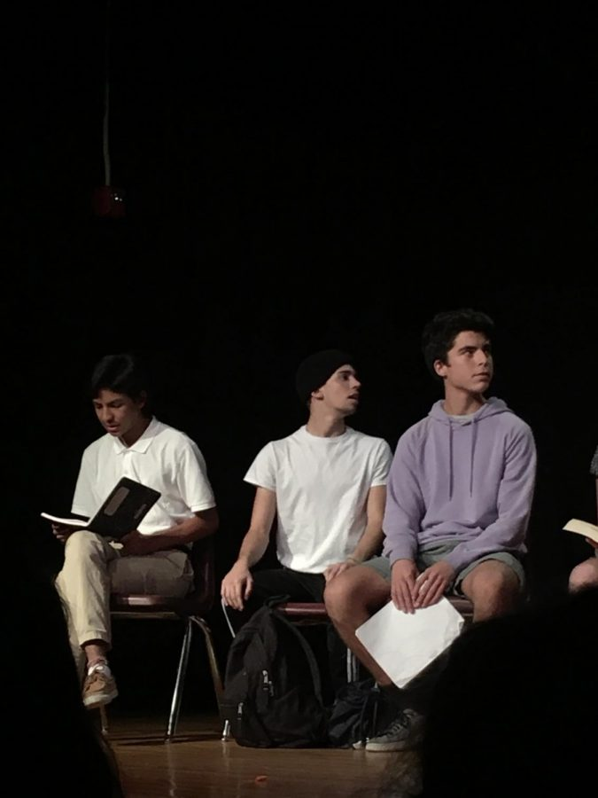Emilio Gutierrez, Tristan Breaux, and Dan Leiferman sit on stage during one of the shorts written by troupe.