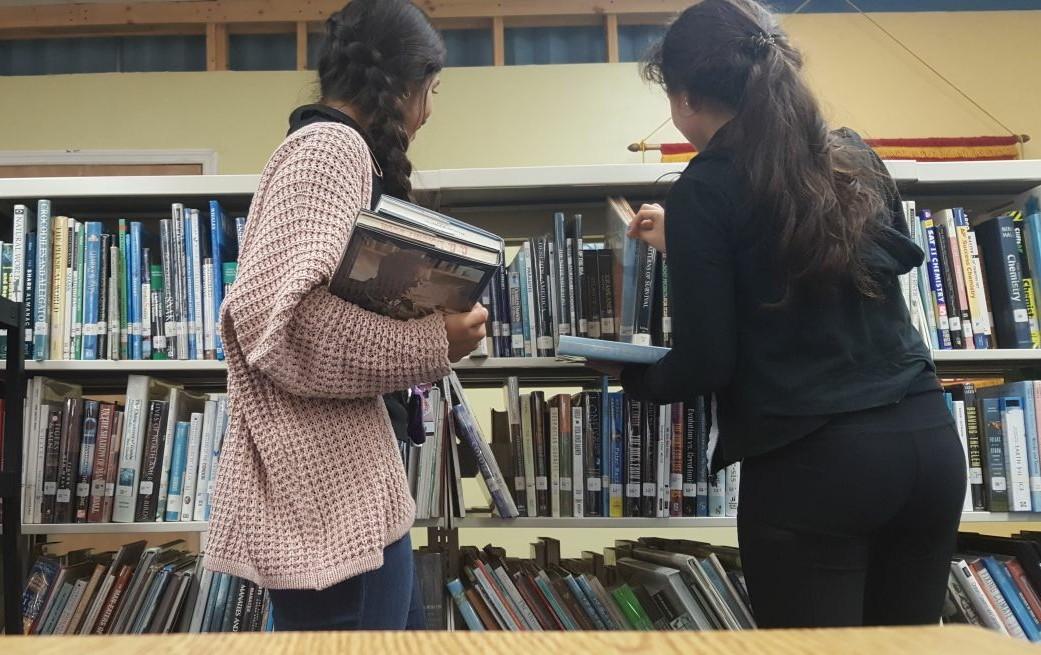 Estudiantes voluntarias haciendo servicio comunitario en la biblioteca.