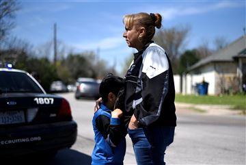 Isaac Machado se esconde detrás de su sombrero contra su madre, Dolores, fuera de la escena de una explosión en la calle Galindo en Austin, Texas.