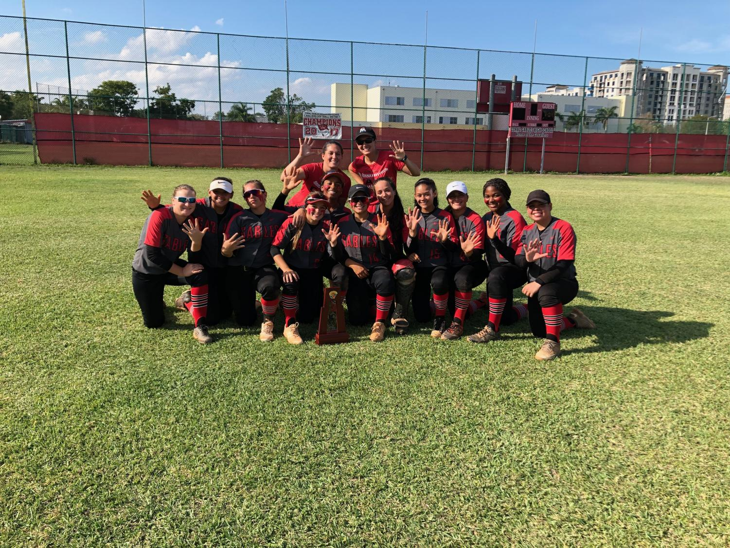 The cavalier softball team posing for a picture after finding out they won districts for the fifth year in a row.