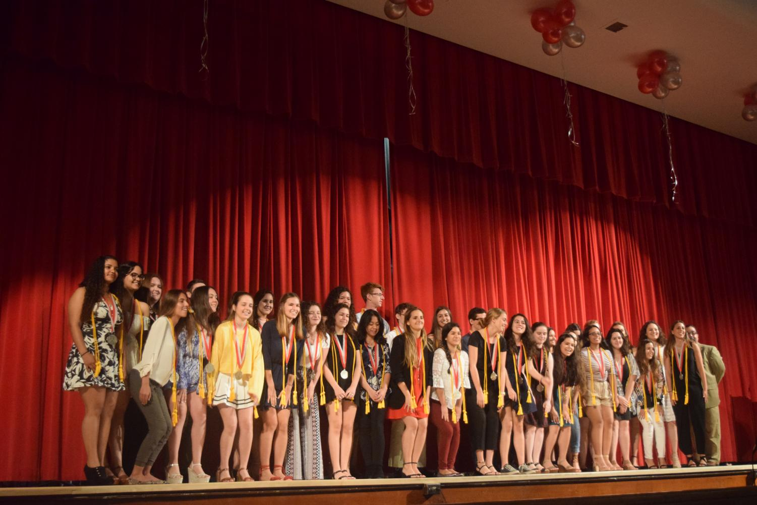 Class of 2019 Summa cum laude students pose for a photo after being awarded their medal and tassel for graduation.