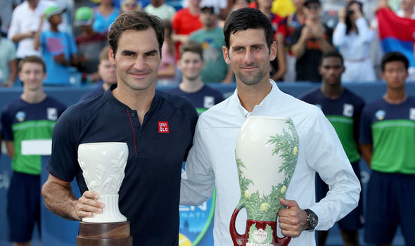 Roger Federer (left) and Novak Djokovic (right) receive their trophies after Djokovic won the Cincinnati Masters tournament on Aug. 19.