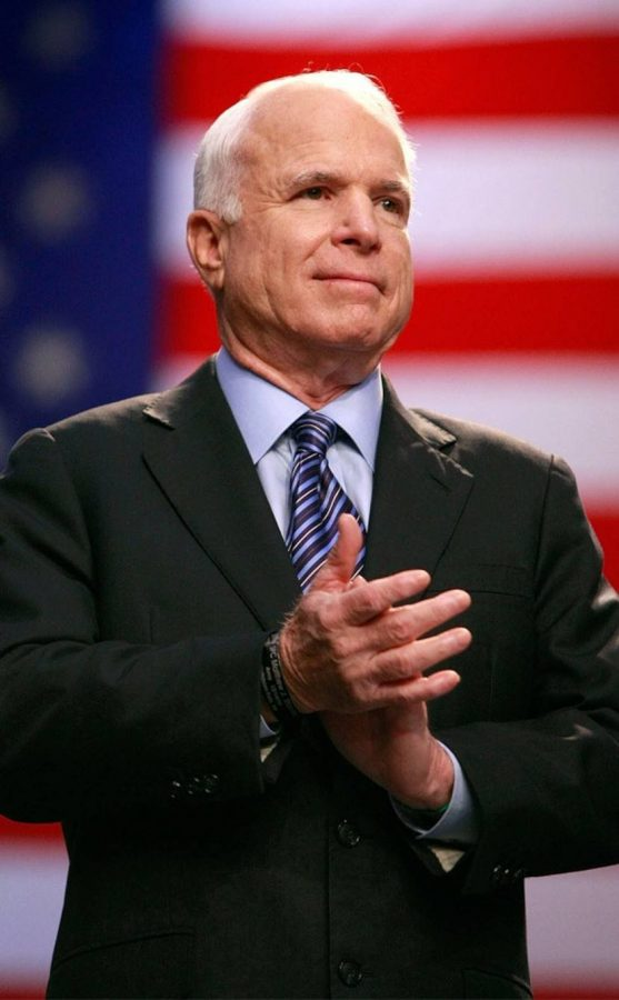 Senator John McCain stands in applause at a political event.