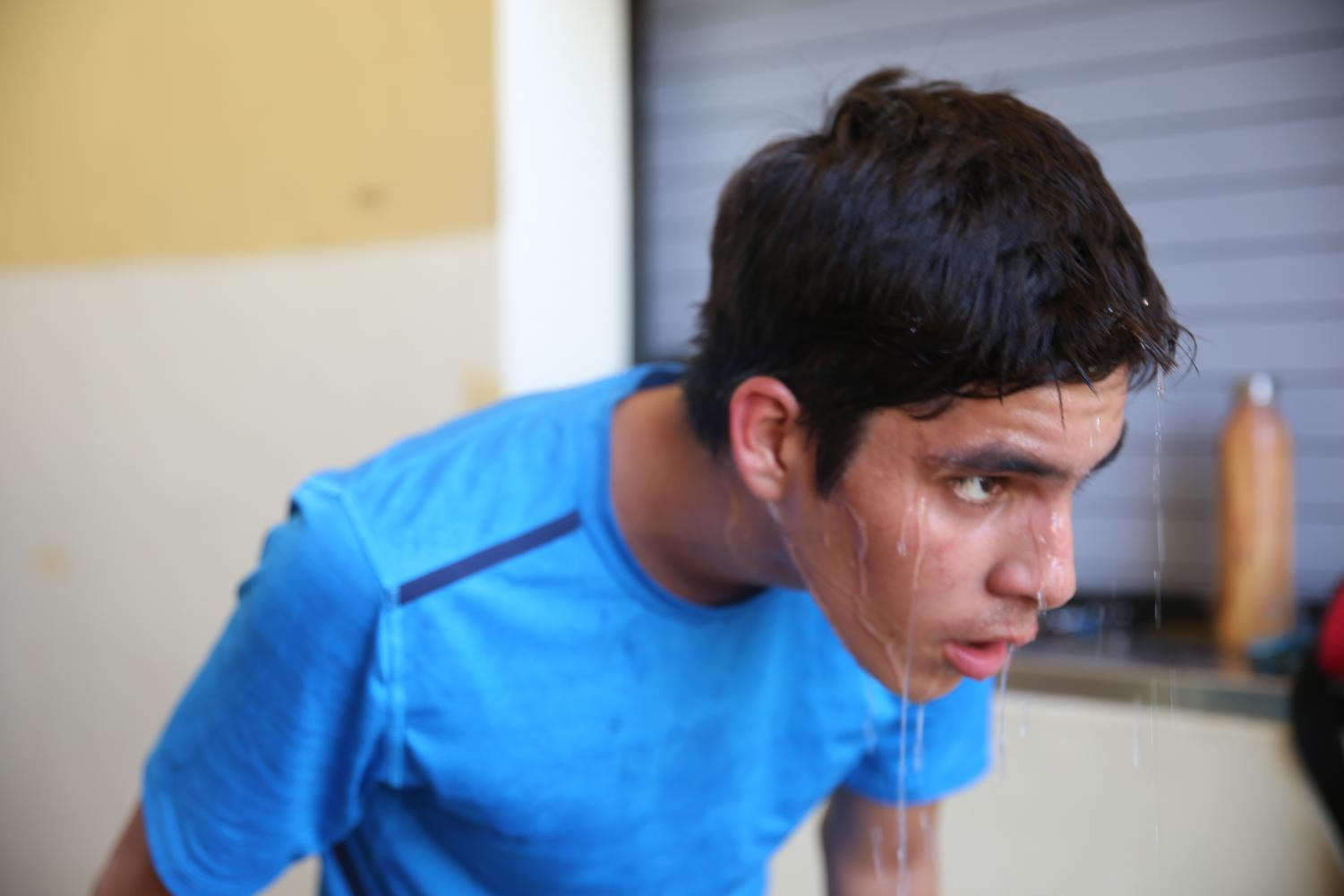 Junior Braulio Gonzales captured as he poured water on his head after cross country practice at the front of the new building.