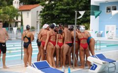 The Coral Gables Cavaliers Swimming Team huddles together in preparation for their swimming meet.