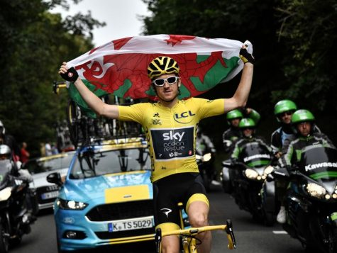 Geraint Thomas leads the Tour de France, waving the Welsh Flag.