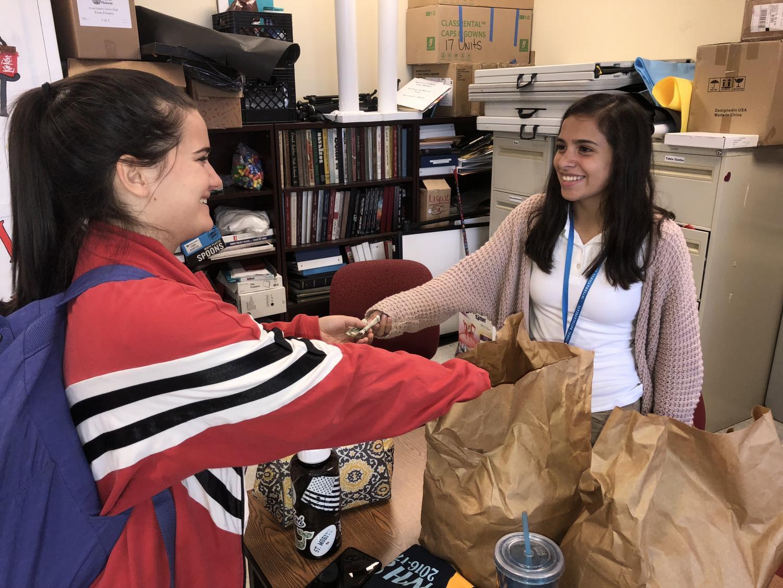 Senior Dominique Babin purchases a delectable ring of bread from junior Jimena Romero.
