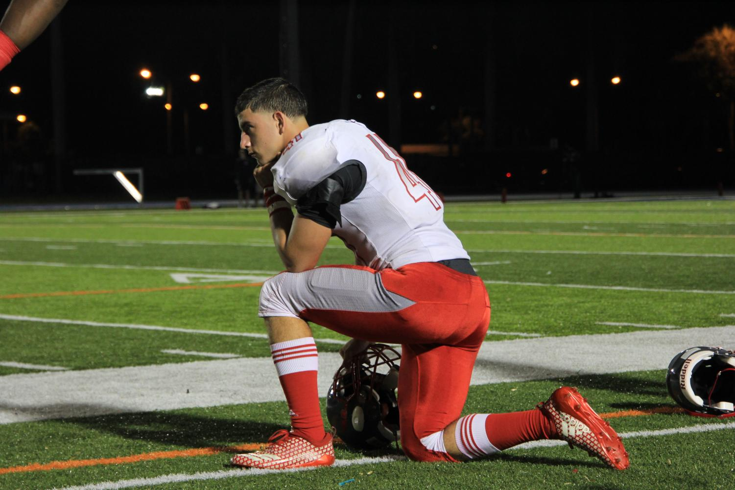 A+resting+football+player+observes+the+field+as+his+teammates+play+against+their+rival%2C+the+Columbus+Explorers.++