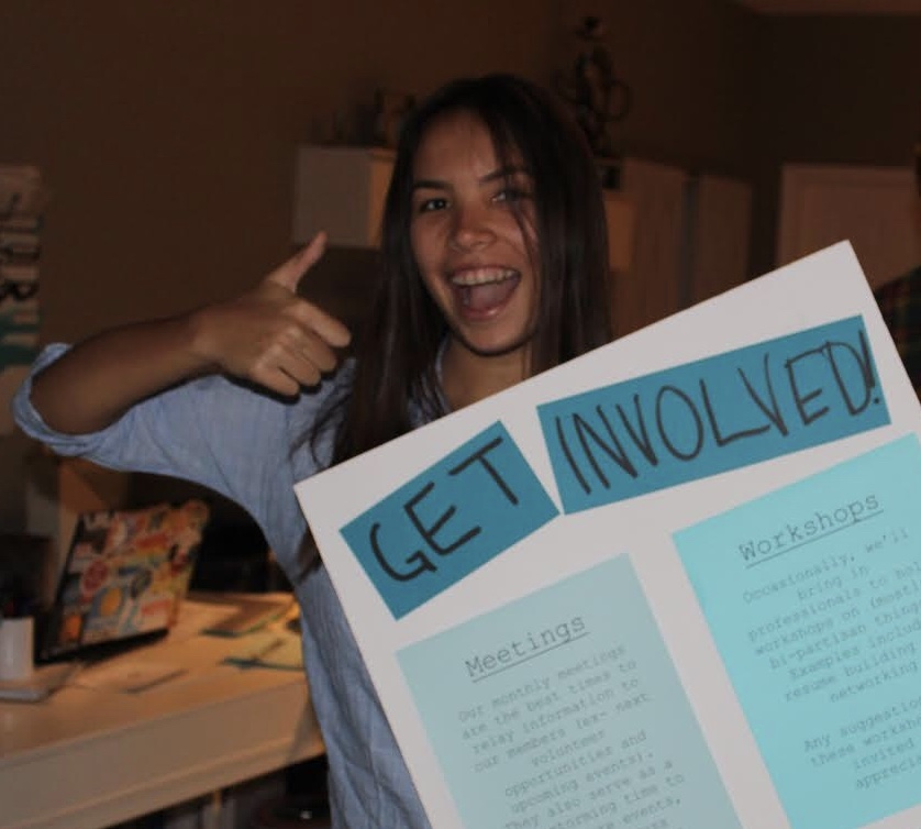 Leus-Oliva stands with a poster promoting the campaign she was working on.