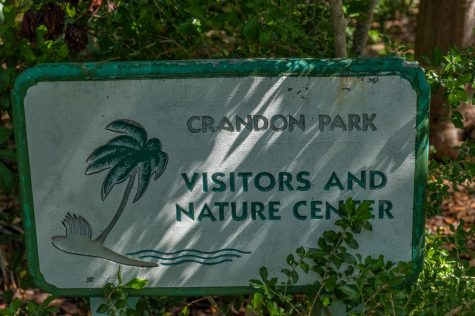 A small sign, partially hidden in the bushes, greets Nature Center visitors.